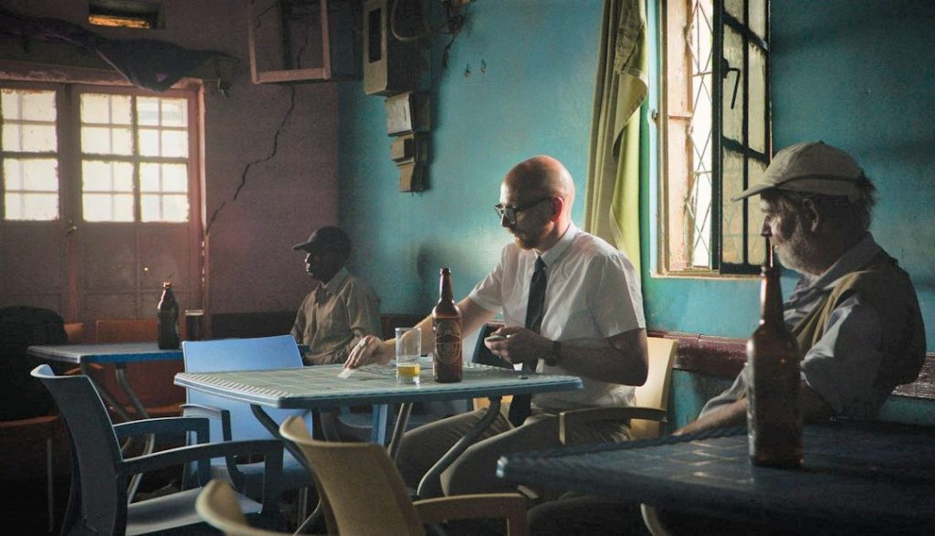FEATURED IMAGE: A still from Cold Case Hammarskjold – the tired hack shuffles the deck and drinks in a moodily lit African tavern. Picture: Tore Vollan